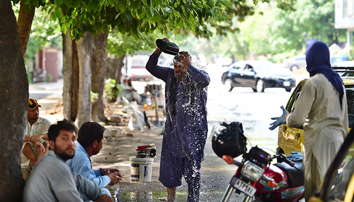 A Pakistani taxi driver showers himself with water on a hot summer day in Islamabad. Photo: AFP