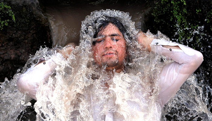 A man reacts as he cools off from the hot and sunny weather, under a water pipe from a canal on the outskirts of Peshawar. Photo: Reuters