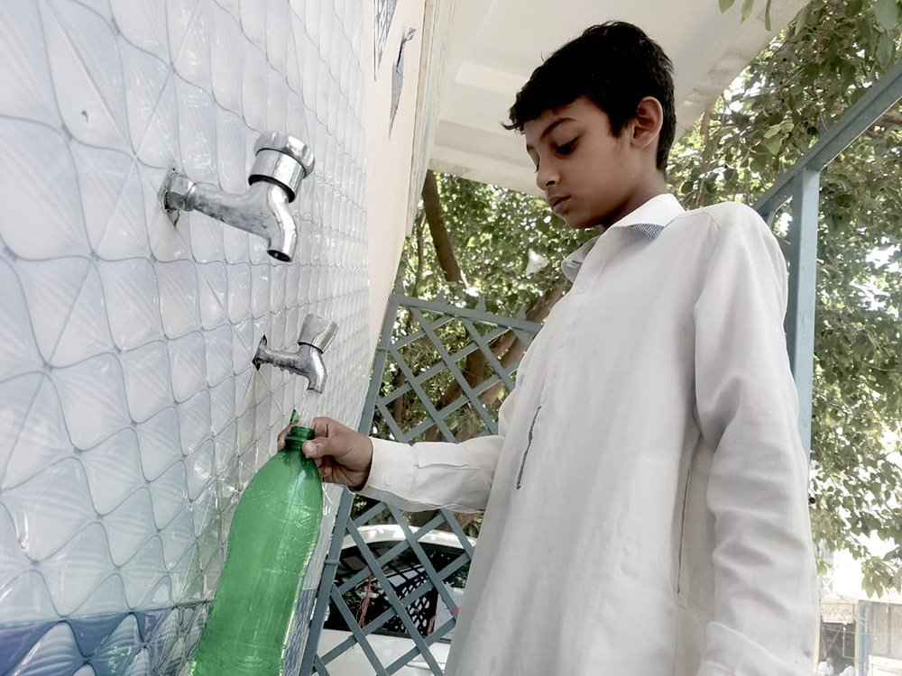 A child is seen filling water from a filtration plant in Peshawar. Photo: Author