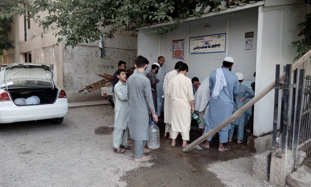 People wait in line at the filtration plant in Peshawar. Photo: Author