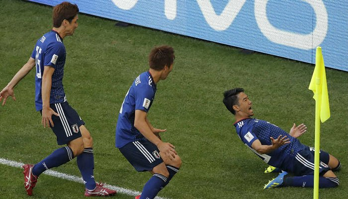 45d5a14aa Japan Shinji Kagawa celebrates with teammates after scoring the opening  goal against Colombia. Photo  AFP