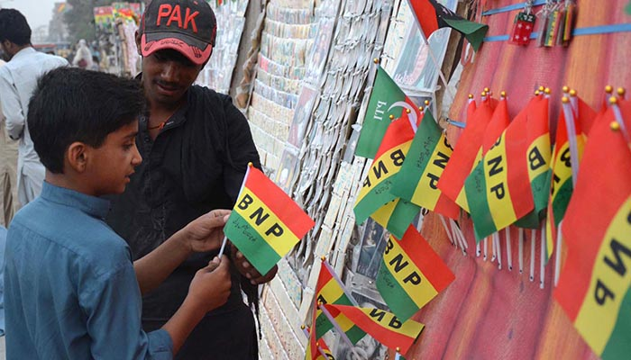 BNP supporter boy buying part flag from roadside vendor during election campaign for upcoming General Election 2018. Photo: INP