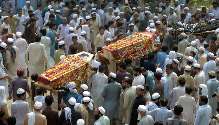 Pakistani residents carry the coffins of blast victims, who were killed in a suicide bombing at an election rally, during their funeral in Peshawar on July 11, 2018. Photo: AFP