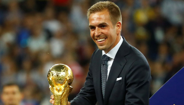 Former Germany player Philipp Lahm places the World Cup trophy onto a podium on the stage for the presentation. Photo: REUTERS