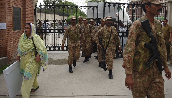 A Pakistani presiding officer (C) carries a voting material as she comes out alongwith army soldiers at the voting materials distribution centre in Rawalpindi on July 24, 2018. Photo: AFP