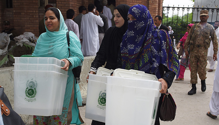 Pakistani presiding officers carry ballot boxes as they come out from the voting material distribution centre in Rawalpindi on July 24, 2018. Photo: AFP