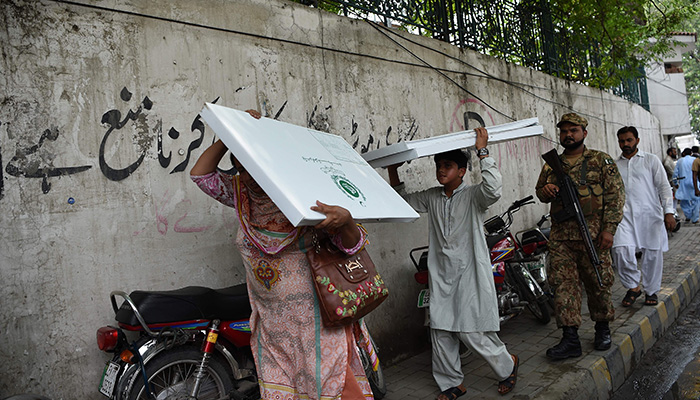 Pakistani polling centre officers with a young boy carry the election material as an army soldier escorts them as they come out from a voting material distribution centre in Lahore on July 24, 2018. Photo: Reuters