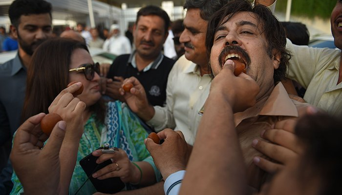 Supporters of Imran Khan, offer sweets to each others after the parliament elected Imran Khan as a Prime Minister of Pakistan, in Islamabad on August 17, 2018 - Photo: AFP