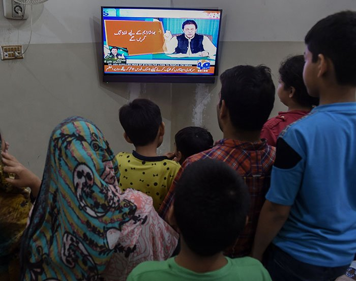 Pakistani family watch a television broadcasting the speech of newly appointed Pakistani Prime Minister Imran Khan as he addresses the nation - Photo: AFP