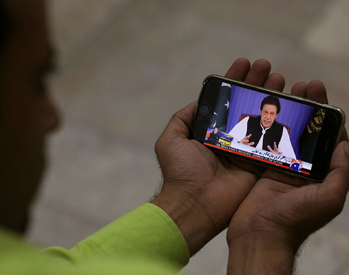 A journalist poses with a cell phone displaying Imran Khan, Prime Minister of Pakistan, speaking to the nation in his first televised address - Photo: Reuters