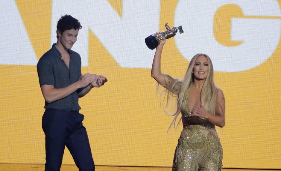 Jennifer Lopez accepts the Michael Jackson Video Vanguard Award as presenter Shawn Mendes applauds