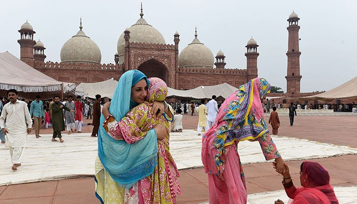 Pakistani women hug each other after Eid al-Adha prayers at the Badshahi Mosque in Lahore on August 22, 2018. Photo: AFP