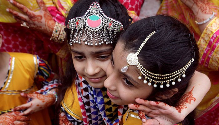 Children with traditional jewelry hug each other during Eid al-Adha celebration in Lahore, Pakistan August 22, 2018. Photo: Reuters