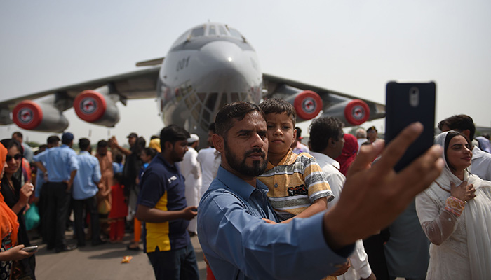 A man takes selfie pictures with his son in front of a plane during celebrations to mark the country's Defence Day at the Nur Khan airbase in Rawalpindi on September 6, 2018 - AFP