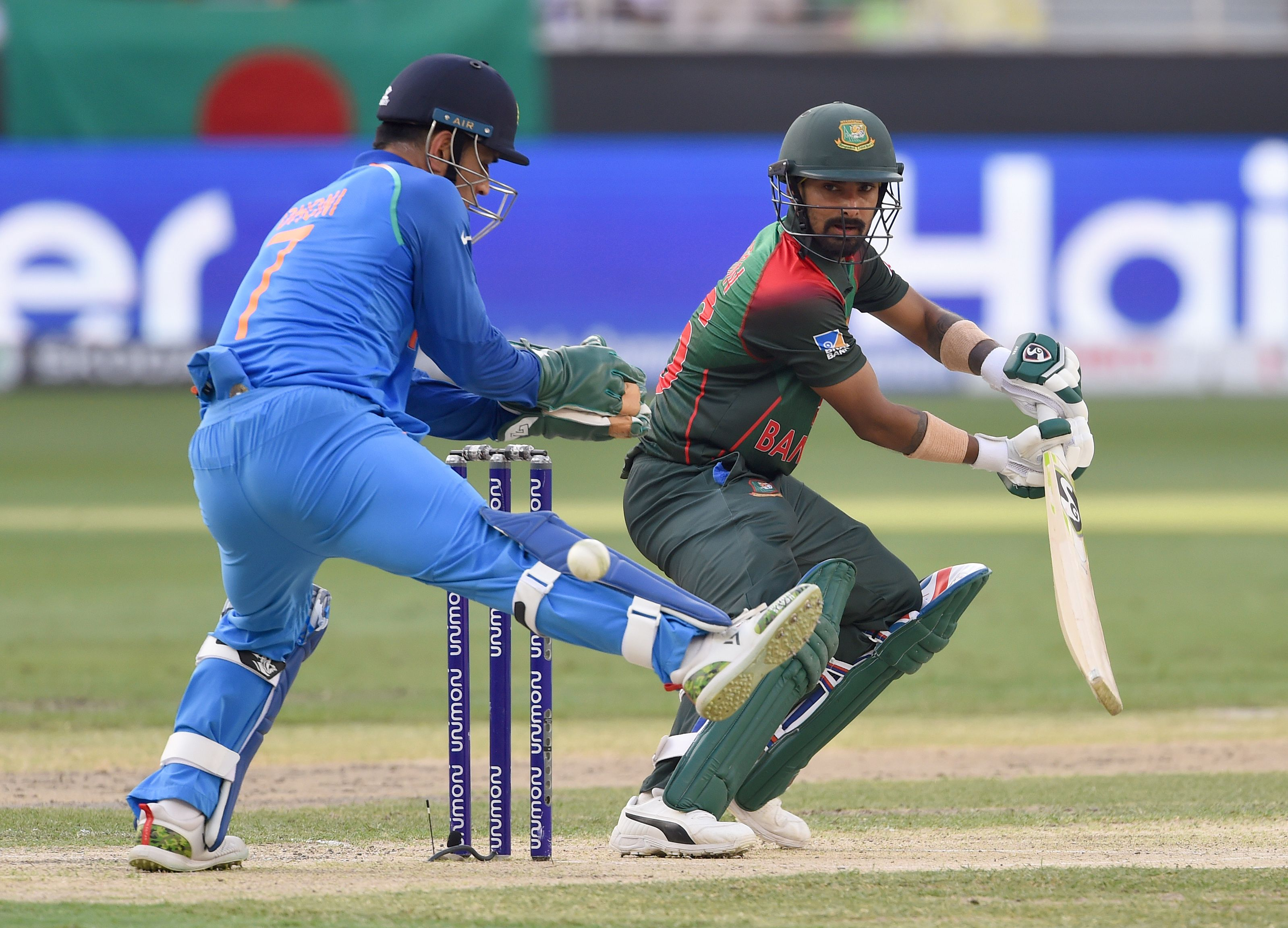 Bangladesh batsman Liton Das plays a shot as Indian wicketkeeper Mahendra Singh Dhoni (L) looks on during the final one day international (ODI) Asia Cup cricket match between Bangladesh and India at the Dubai International Cricket Stadium in Dubai on September 28, 2018. / AFP