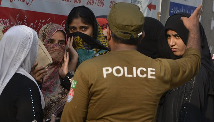 A Pakistani policeman guides women outside a polling station during the by-election in Lahore, Pakistan, October 14, 2018. AFP/Arif Ali