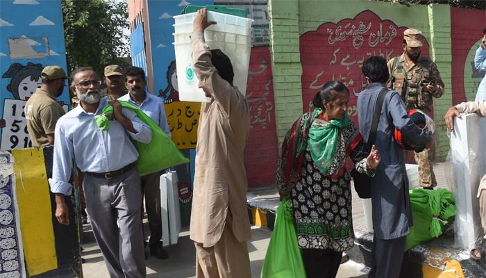 Pakistani election presiding officers carry election materials for the by-election in Lahore, Pakistan, October 13, 2018. AFP/Arif Ali