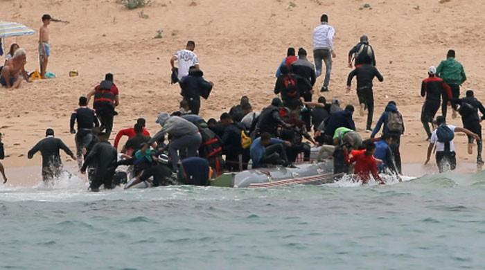 Hundreds of migrants storm Spanish enclave in North Africa, one dies
