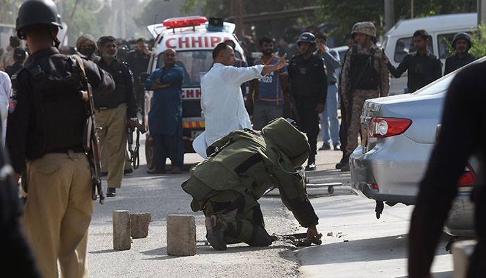 A bomb disposal squad member warns onlookers before checking a bag belonging to an attacker outside the Chinese consulate after the attack in Karachi on November 23, 2018 - AFP