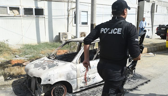 A Pakistani police commando walks past a burned out vehicle outside the Chinese consulate after an attack in Karachi on November 23, 2018 - AFP