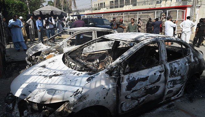 Pakistani security personnel stand next to burned out vehicles in front of the Chinese consulate after an attack in Karachi on November 23, 2018 - AFP