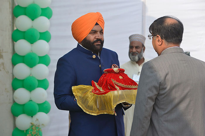 Indian Member of Parliament Gurjeet Singh Aujla (C) holds a pot containing water from the Sikh Golden Temple in Amritsar as he takes part in a groundbreaking ceremony for the Kartarpur Corridor. Photo: AFP