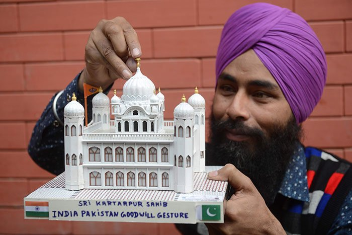 Indian artist Gurmeet Singh poses with a paper model of the Gurdwara Kartarpur Sahib in Pakistan -- the focus of the Kartarpur corridor between India and Pakistan -- in Amritsar on November 28, 2018. Photo: AFP