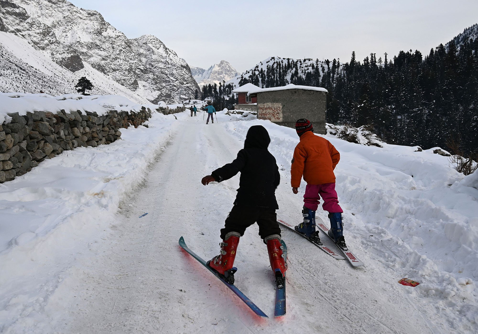 In this picture taken on January 29, 2019, Pakistani children ski on a snow-covered street next to their homes near the slopes where the CAS Karakoram International Alpine Ski Cup was taking place at the Pakistan Air Force-owned and operated Naltar Ski Resort, some 25km north of Gilgit in Pakistan´s remote mountainous north. Photo AFP