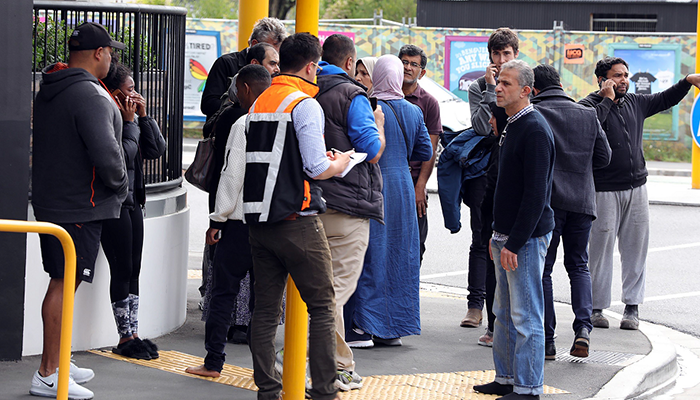 This picture released by Radio New Zealand shows residents gathering close to the mosque after a firing incident in Christchurch. PHOTO: AFP