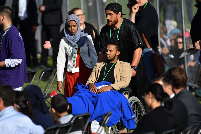 A man is wheeled into the family area in front of the stage during a national remembrance ceremony at North Hagley Park in Christchurch, New Zealand, March 29, 2019. AFP/Marty Melville