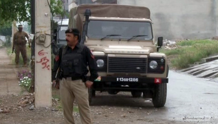 A policeman stands guard near the site of the operation. Photo: Geo News screengrab