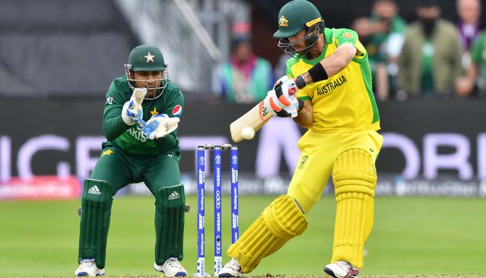 Australia´s David Warner (R) is watched by Pakistan´s captain Sarfaraz Ahmed as he plays a shot. Photo: AFP