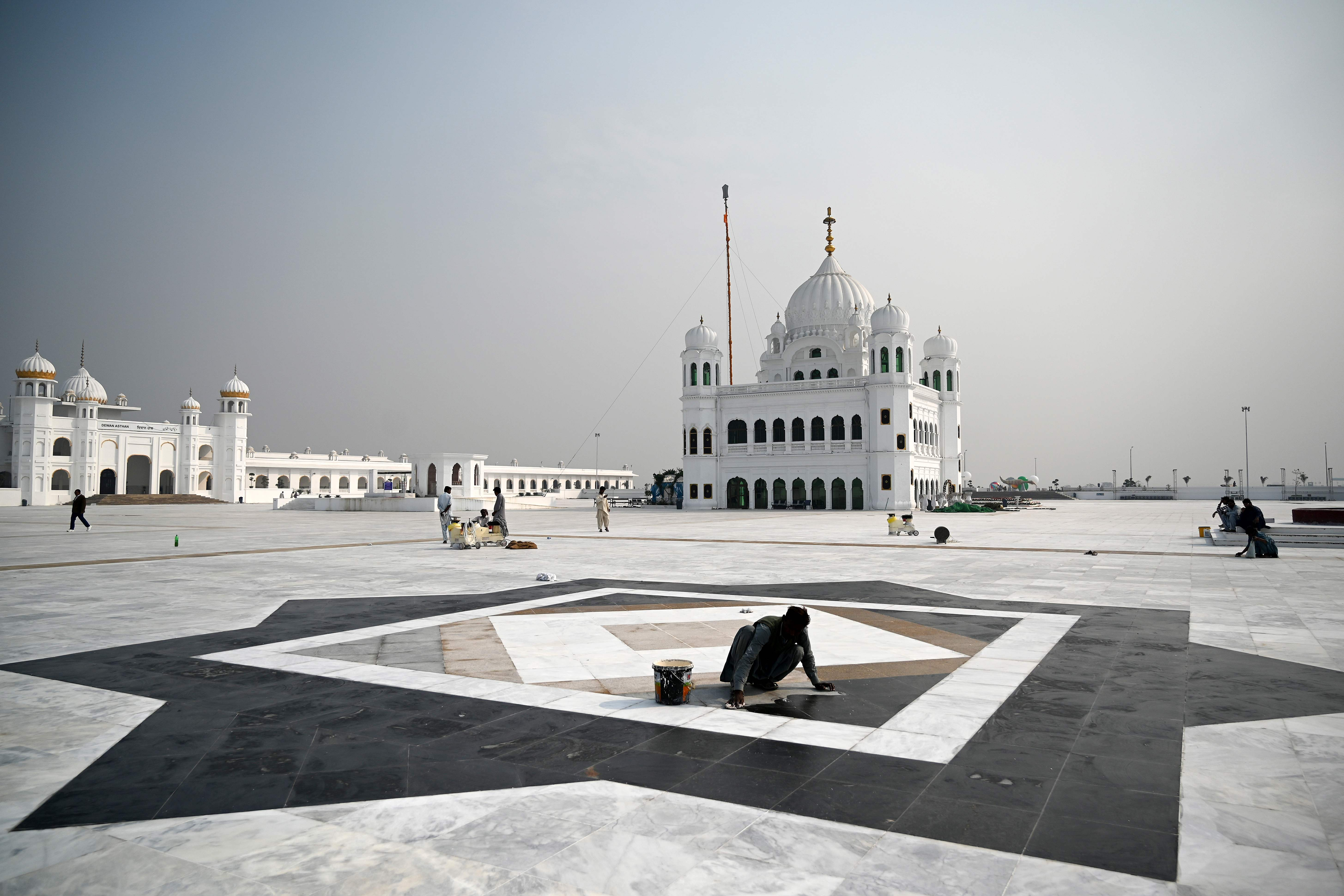 In this picture taken on November 6, 2019 workers shine a floor at the Shrine of Baba Guru Nanak Dev at the Gurdwara Darbar Sahib ahead of its opening, in the Pakistani town of Kartarpur near the Indian border. — AFP Photo
