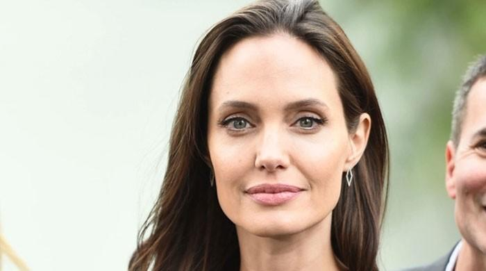 Angelina Jolie signs a tattoo of her own face on a British actor's arm