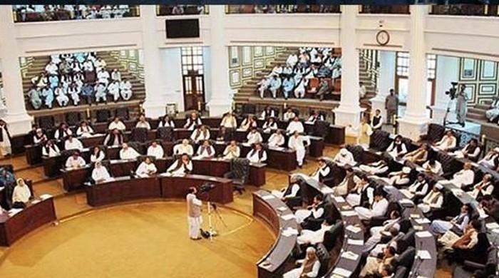 KP Assembly opposition members stand on seats to register protest