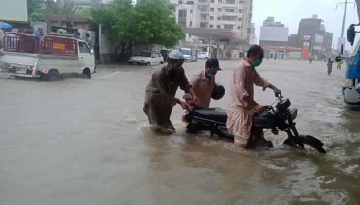 Citizens stuck in the mid of an inundated road after the torrential rains wrecked havoc in the city. Photo: Geo.tv