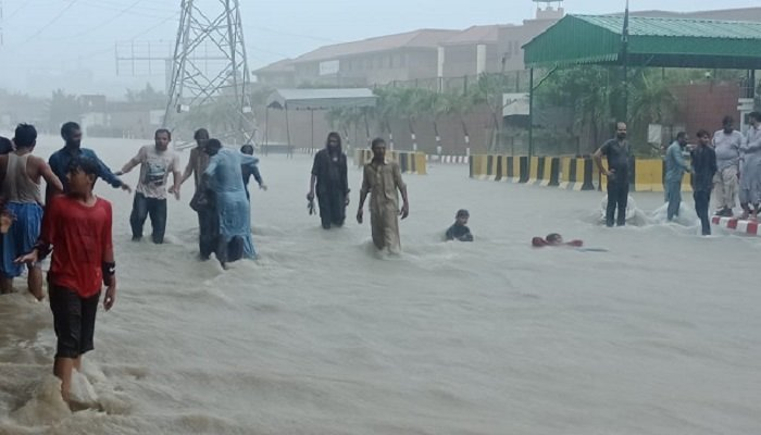 People standing out on roads after rains in Karachi break a 9-year-old record . Photo: Geo.tv