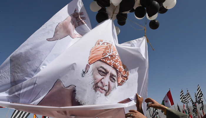 Opposition supporters carry a banner featuring an image of the leader of Pakistan Democratic Movement (PDM), Maulana Fazlur Rehman during an anti-government rally in Quetta on October 25, 2020. — AFP