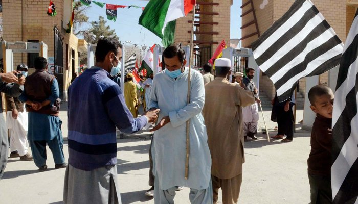 Supporters of Pakistan Democratic Movement (PDM) are sanitizing their hands as a preventive measures against the spread of the coronavirus (COVID- 19), on their arrival to attend public gathering meeting held at Ayub Stadium in Quetta on Sunday, October 25, 2020. — PPI