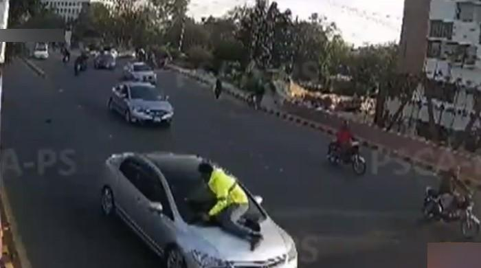 Watch: Lahore man puts traffic warden's life at risk after being asked to pull over