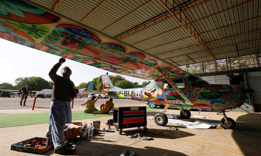 Men paint Pakistani truck art on a two-seater Cessna aircraft at general aviation area at Jinnah International Airport, Karachi, Dec 30, 2020. — Reuters