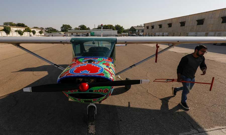 A technician walks past a two-seater Cessna aircraft painted with Pakistani truck art at Jinnah International Airport, Karachi, Dec 30, 2020. — Reuters