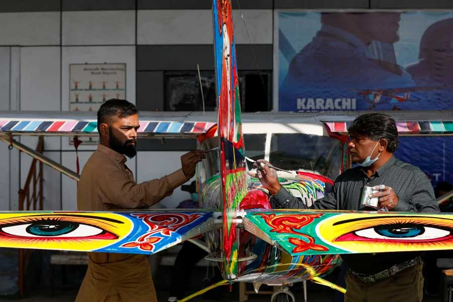 Haider Ali, 40 (R) and his student paint Pakistani truck art on a two-seater Cessna aircraft at general aviation area at Jinnah International Airport, Karachi, Dec 30, 2020. — Reuters