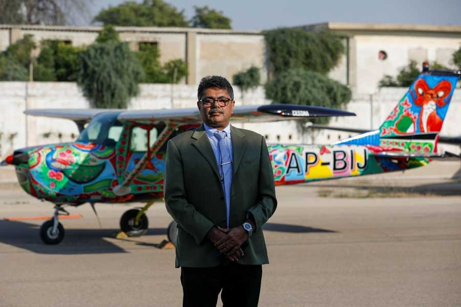 Imran Aslam Khan, Chief Operating Officer of Sky Wings, poses with a two-seater Cessna aircraft painted with Pakistani truck art in the background, at Jinnah International Airport, Karachi, Dec 30, 2020. — Reuters
