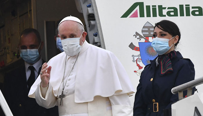 Pope Francis boards a plane as he departs to Iraq
