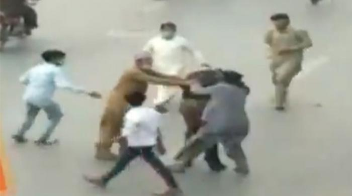 Watch: Lahore policeman flees for his life as protesters beat him with sticks