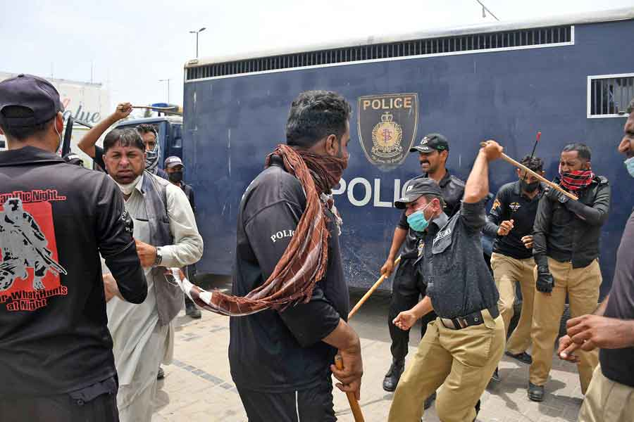 A protester attempts to get away as police personnel charge with batons during a protest against the anti-encroachment operation at Aladdin Park, Gulshan-e-Iqbal, Karachi, on June 15, 2021. — Online photo by Sabir Mazhar