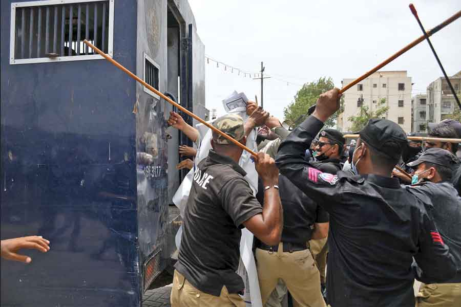 Police personnel charging with batons at protesters to disperse them and continue the anti-encroachment operation at Aladdin Park, Gulshan-e-Iqbal, Karachi, on June 15, 2021. — Online photo by Sabir Mazhar