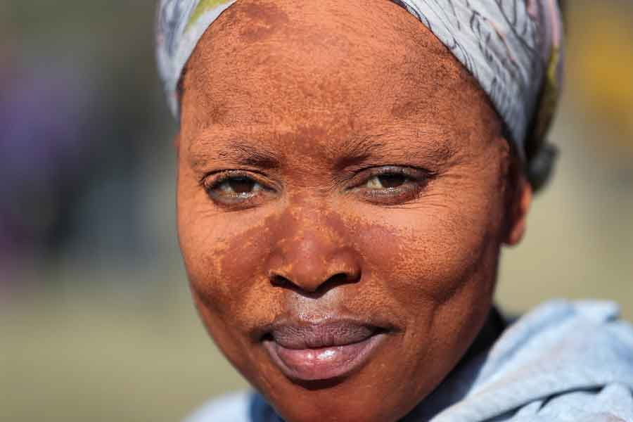 A woman using clay to apply on her face to protect her skin from the sun looks on as fortune seekers flock to the village after pictures and videos were shared on social media showing people celebrating after finding what they believe to be diamonds, in the village of KwaHlathi outside Ladysmith, in KwaZulu-Natal province, South Africa, June 14, 2021. — Reuters/Siphiwe Sibeko