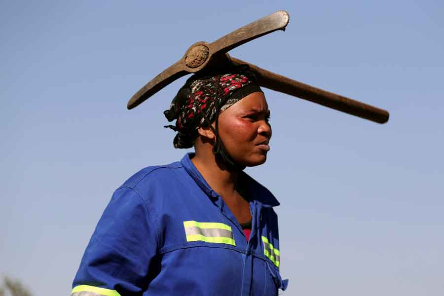 A woman arrives carrying a pickaxe on her head as fortune seekers flock to the village of KwaHlathi in search of what they believe to be diamonds, outside Ladysmith, KwaZulu-Natal province, South Africa June 14, 2021. — Reuters/Siphiwe Sibeko